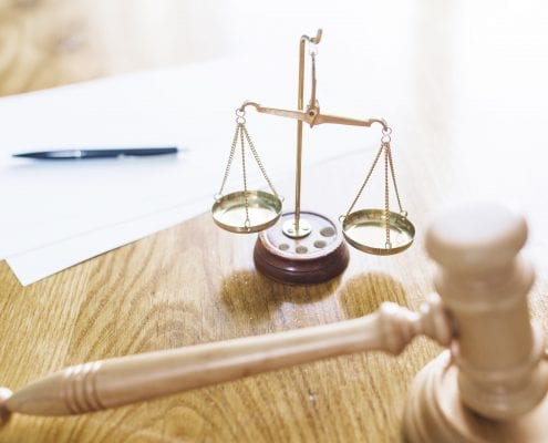 Gavel and scales on a table representing our personal injury verdicts and workers comp settlements page.