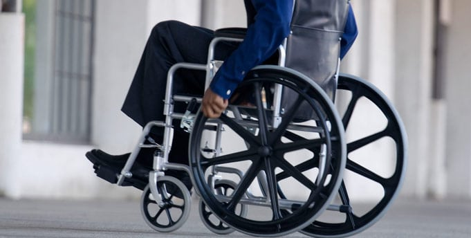 Man in a blue suit and a wheelchair with a social security disability claim.