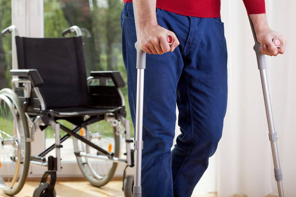 nh workers compensation attorney helping man in wheelchair after a work injury.