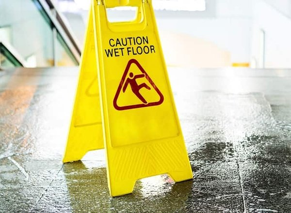 Yellow caution wet floor sign at the top of manchester nh building stairs with a very wet floor likely to cause a slip and fall injury.